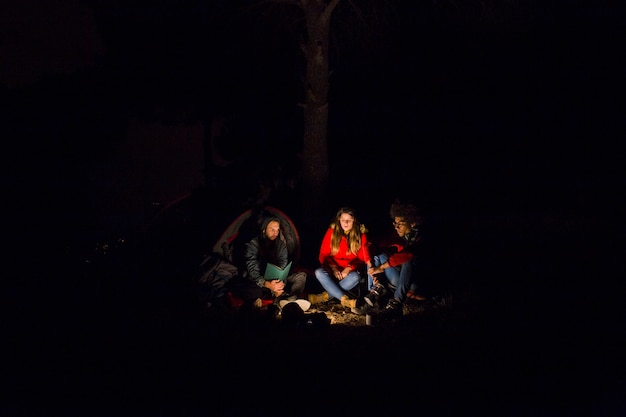 Joven pareja y su amigo disfrutando en el campamento por la noche