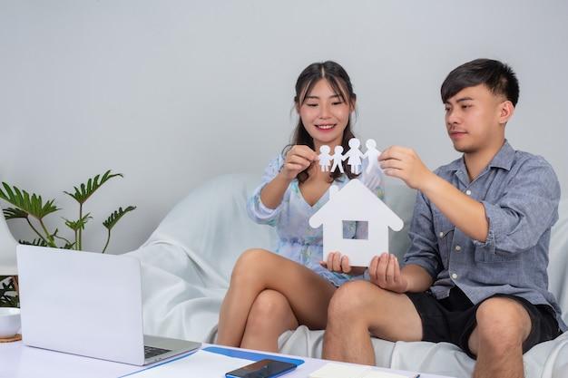 Joven pareja está trabajando desde su casa, mientras que la niña está sosteniendo la casa de papel en el sofá.
