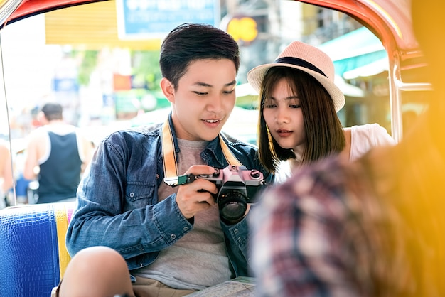 Joven pareja de turistas asiáticos que viajan en taxi local tuk tuk en khao san road, bangkok, tailandia