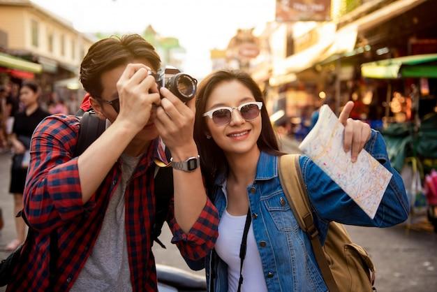 Joven pareja de turistas asiáticos tomando una foto en bangkok, tailandia
