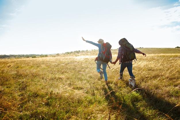Joven pareja de viajeros caminando en campo con perro pug