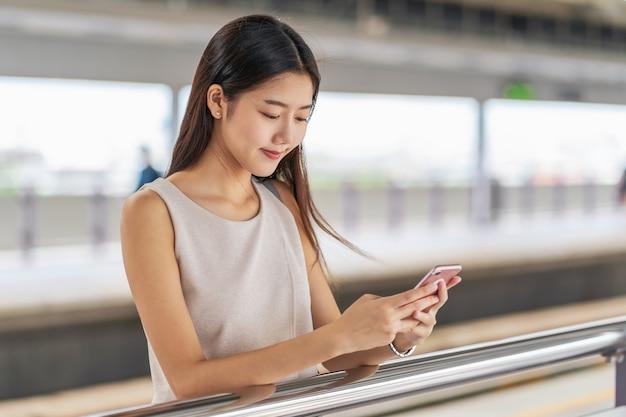 Joven pasajera asiática utilizando la red social a través de un teléfono móvil inteligente en el metro cuando viaja en la gran ciudad