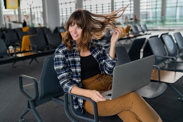 Joven pasajera con laptop sentada en el hall de la terminal mientras espera su vuelo