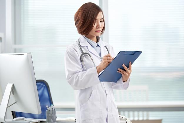 Joven pasante médico llenando papeles de informe