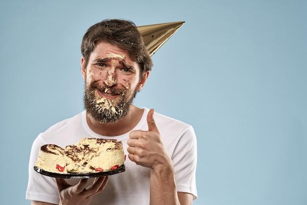 Un joven con un pastel de cumpleaños cayó sobre su rostro con un pastel, su rostro en un pastel