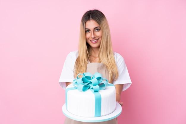 Joven pastelera uruguaya con un gran pastel sobre pared rosa aislado con expresión feliz