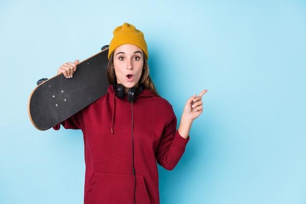 Joven patinador mujer caucásica aislada apuntando hacia el lado