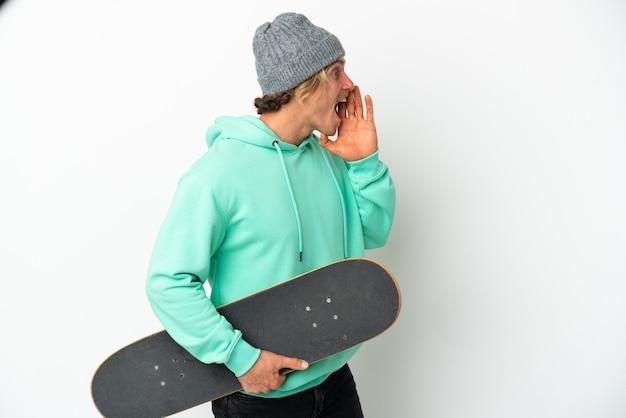 Joven patinador rubio aislado en la pared blanca gritando con la boca abierta hacia un lado