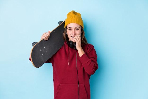 Joven patinadora mujer caucásica aislada morderse las uñas, nerviosa y muy ansiosa.