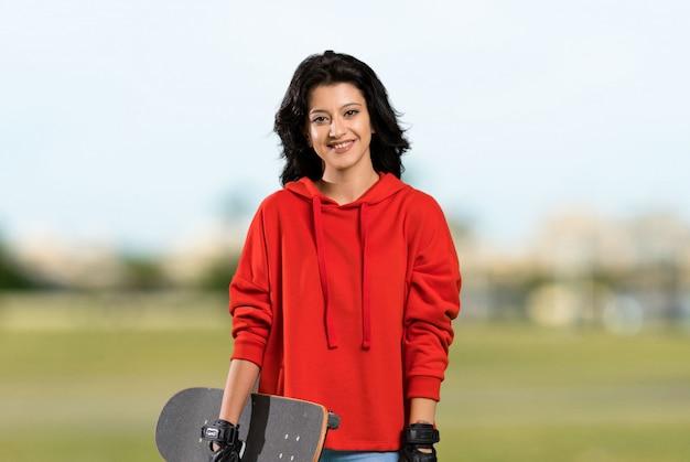 Joven patinadora mujer sonriendo mucho al aire libre