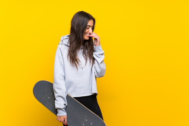 Joven patinadora sobre pared amarilla aislada sonriendo mucho