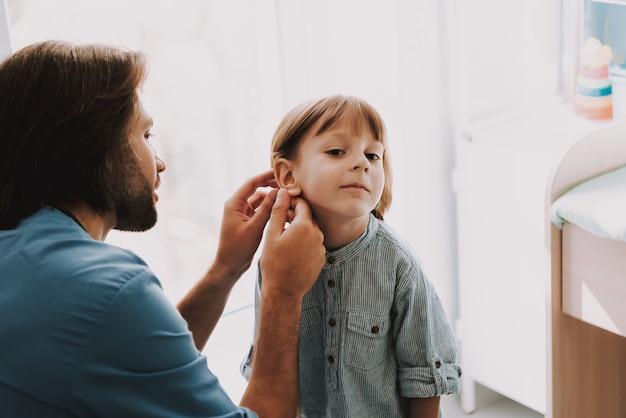 Joven pediatra examinando el oído de un niño en la clínica
