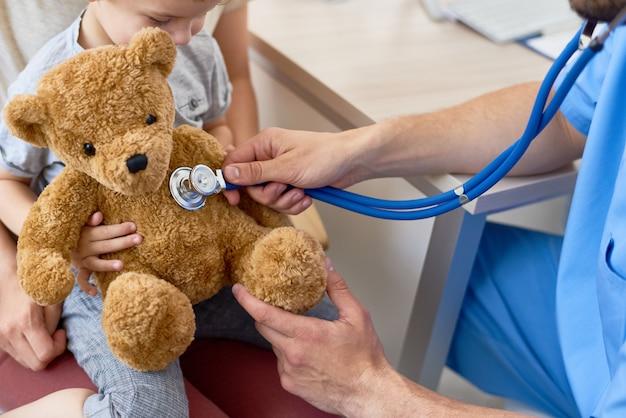 Joven pediatra jugando con pequeño paciente