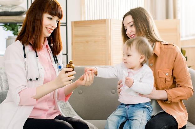 Joven pediatra prescribe y le da un medicamento a la niña enferma, sentada con su madre