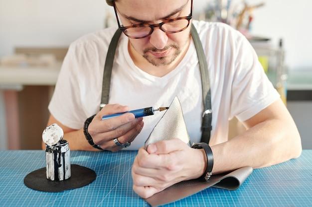 Joven peletero creativo serio aplicando pintura negra en el borde de la pieza de cuero gris mientras está sentado junto a la mesa en el taller
