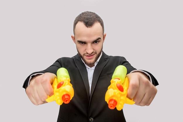 Un joven peligroso en traje sostiene dos pistolas de agua en las manos y las dirige en línea recta. él está enojado y serio.