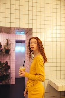 Joven pelirroja concentrada dama rizada de pie en la cafetería