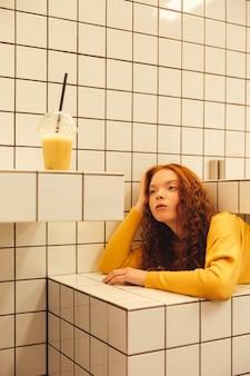 Joven pelirroja concentrada dama rizada sentada en la cafetería