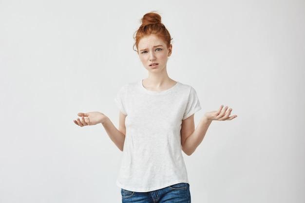 Joven pelirroja disgustado gesticulando mujer confundida discutiendo con un novio. blanco.