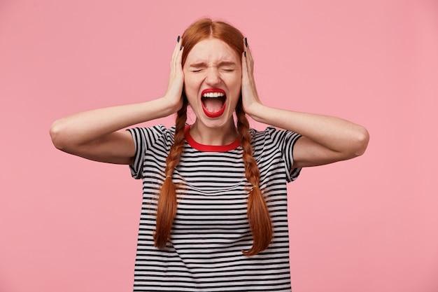 Joven pelirroja enojada con camiseta a rayas, mantiene los ojos cerrados, cierra los oídos con las palmas, muestra un gesto de ignorar, demuestra un fuerte grito o grito, sobre una pared rosa
