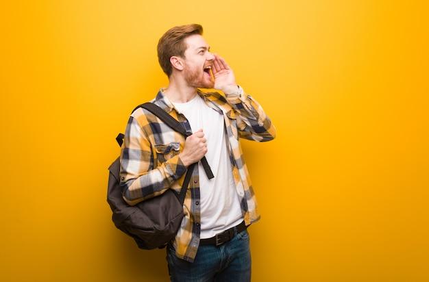 Joven pelirroja estudiante hombre susurrando chisme bajo tono