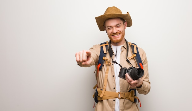 Joven pelirroja explorer hombre alegre y sonriente apuntando al frente. sosteniendo una cámara de fotos.