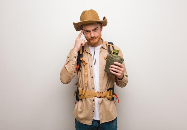 Joven pelirroja explorer hombre pensando en una idea. él está sosteniendo una cantimplora.