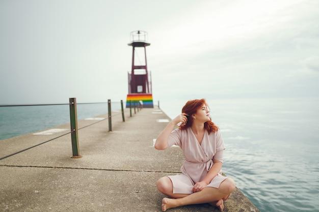 Joven pelirroja en un gran sombrero redondo y vestido rosa sentado en el muelle cerca del océano