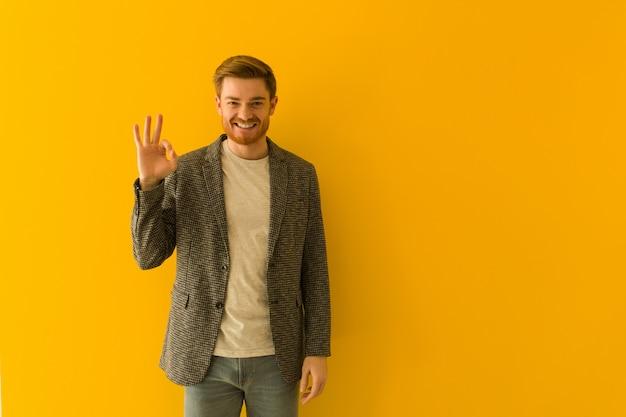 Joven pelirroja hombre de negocios alegre y confidente haciendo gesto bien
