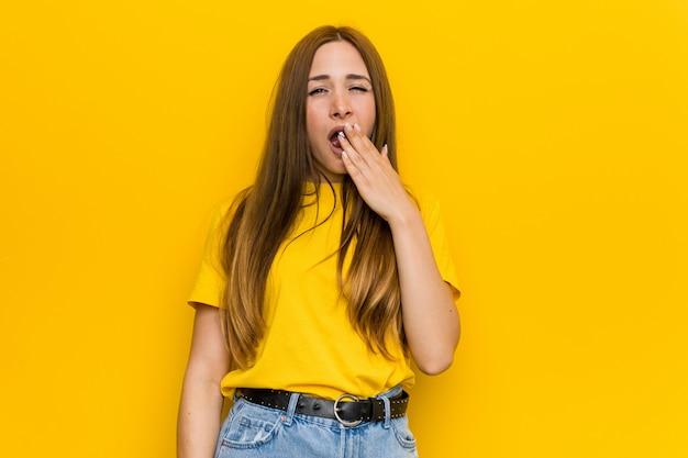 Joven pelirroja jengibre mujer bostezando mostrando un gesto cansado cubriendo la boca con la mano.