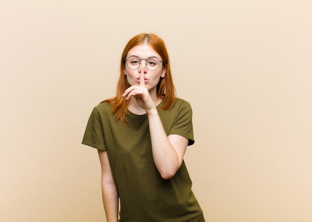 Joven pelirroja linda mujer pidiendo silencio y silencio, gesticulando con el dedo frente a la boca, diciendo shh o guardando un secreto