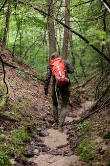 Joven pelirroja mujer de pelo largo viaja en verano bosque nublado