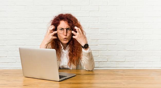 Joven pelirroja mujer rizada trabajando con su computadora portátil molesto gritando con manos tensas