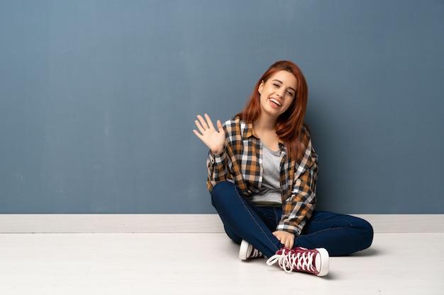 Joven pelirroja mujer sentada en el piso saludando con la mano con expresión feliz