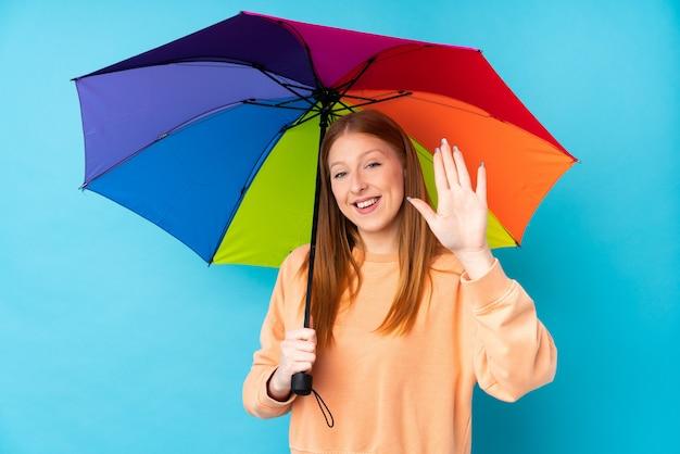 Joven pelirroja mujer sosteniendo un paraguas sobre pared aislada saludando con la mano con expresión feliz