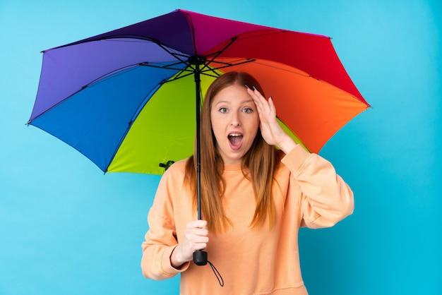 Joven pelirroja mujer sosteniendo un paraguas sobre la pared aislada con sorpresa y expresión facial conmocionada