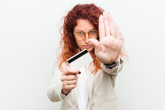 Joven pelirroja mujer sosteniendo una tarjeta de crédito de pie con la mano extendida que muestra la señal de stop
