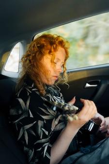 Joven pelirroja mujer tocando la guitarra en coche