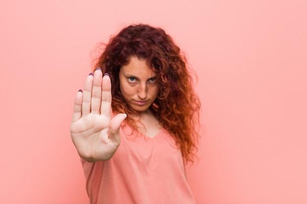 Joven pelirroja natural y auténtica mujer de pie con la mano extendida que muestra la señal de stop