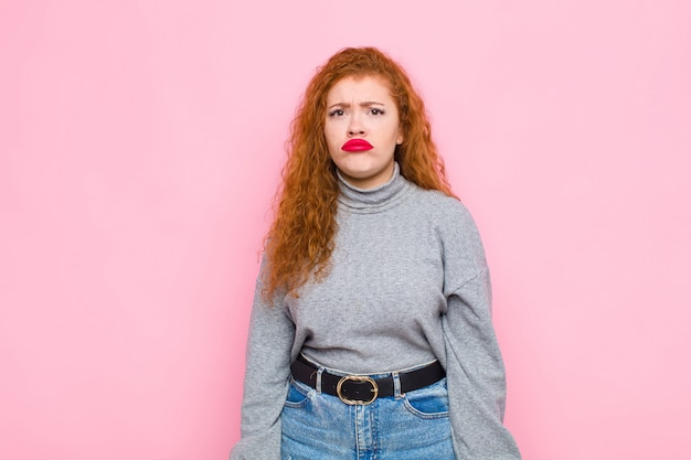 Joven pelirroja que se siente triste y llorona con una mirada triste, llorando con una actitud negativa y frustrada contra la pared rosa