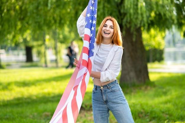 Joven pelirroja sosteniendo la bandera nacional de estados unidos de pie al aire libre en el parque de verano.