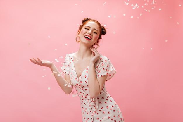 Joven pelirroja vestida de blanco sonríe coquetamente. mujer con sombras de ojos amarillas posando sobre fondo rosa con confeti.