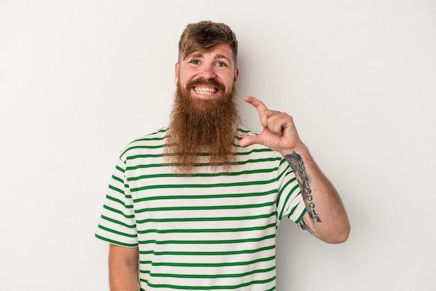 Joven pelirrojo caucásico con barba larga aislado sobre fondo blanco sosteniendo algo pequeño con los dedos índices, sonriente y confiado.