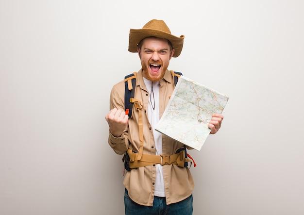 Joven pelirrojo explorador hombre sorprendido y conmocionado sosteniendo un mapa.