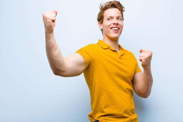 Joven pelirrojo gritando triunfante, luciendo emocionado, feliz y sorprendido ganador, celebrando contra la pared azul