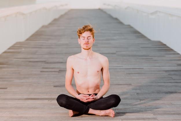 Joven pelirrojo practicando la postura de loto yoga, padmasana, al aire libre en el piso de madera