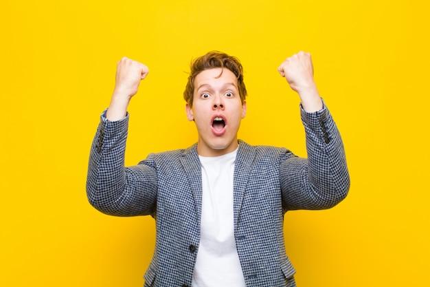 ¡joven pelirrojo que celebra un éxito increíble como un ganador, se ve emocionado y feliz diciendo: ¡toma eso!