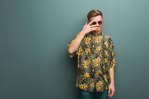 Joven pelirrojo con ropa exótica de verano avergonzado y riendo al mismo tiempo