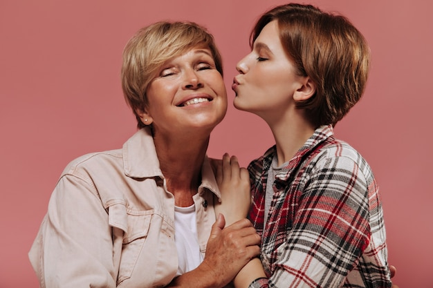 Joven de pelo corto con camisa roja a cuadros besando en la mejilla a su abuela con cabello rubio en chaqueta beige sobre fondo rosa.
