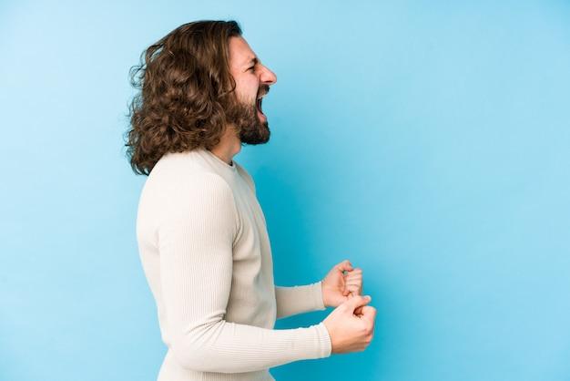 Joven de pelo largo en una pared azul gritando hacia un espacio en blanco